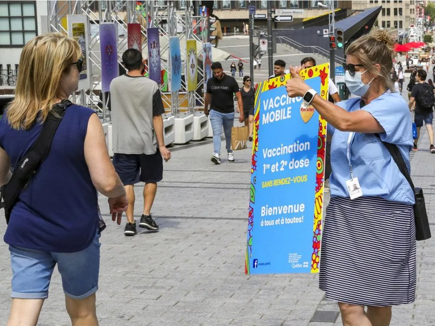 A vaccination worker carries a sign as she tries to recruit people to get vaccinated against COVID-19 at a mobile clinic in Place des Festivals in Montreal Sunday August 8, 2021.