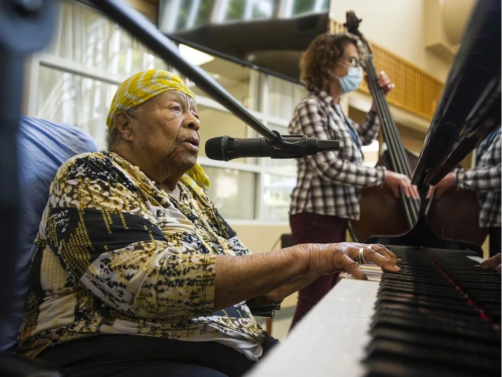 Eve Duke, backed-up by standup bassist Wendy Solloway and drummer Paul Adams, not pictured, plays the grand piano at St. Vincent's Langara care home in Vancouver on June 10.