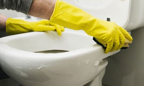 Bathroom Deep Cleaning by Cleaner with yellow gloves