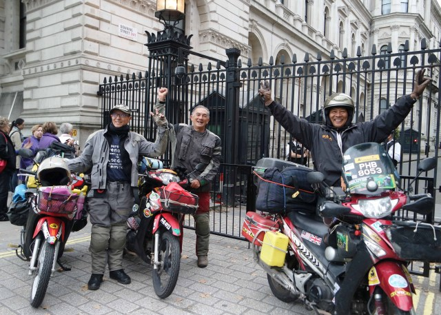 Photos show three men near three motorbikes at No. 10 Downing Street, London, UK. The men are indetified as Eric Lim, Captain BK Lim and Timothy Wooi