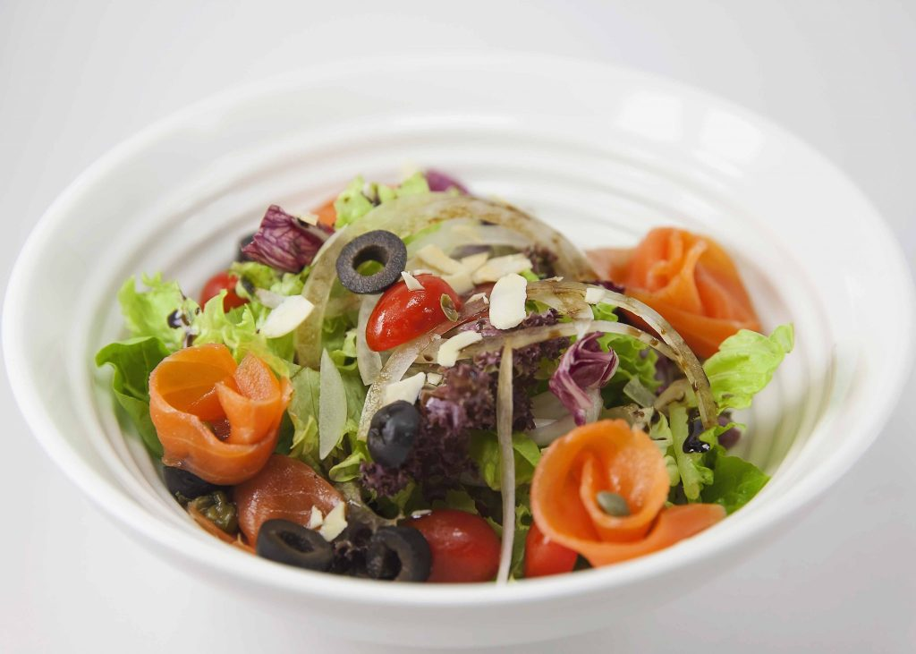Smoke salmon triwl into florets with greens, lettuce, cherry tomato, black pitted olives, onions in a white bowl with a white background