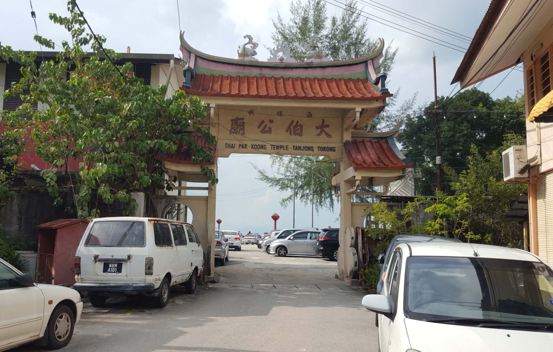 Narrow tarmac road leading to Chinese archway with Chinese characters and words describing Thai Pak Koong temple, Tajung Tokong. Beyond this is the Penang Avatar Secret Garden besides Tua Pek Khong Temple, Tanjung Tokong, George Town, Penang. Photo taken on 11 June 2017 by Doris Lim of www.smartdory.com