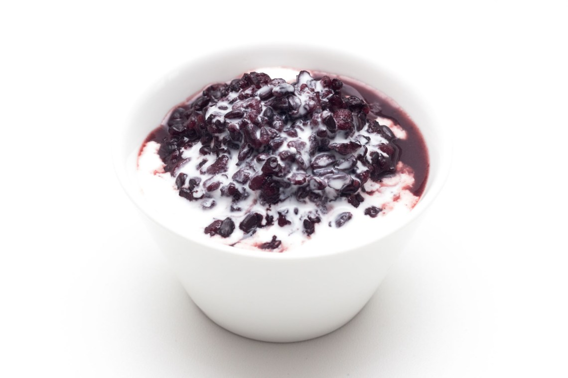 Photo shows a white bowl against a white background and black purplish glutinous rice dessert with white coconut milk on top.