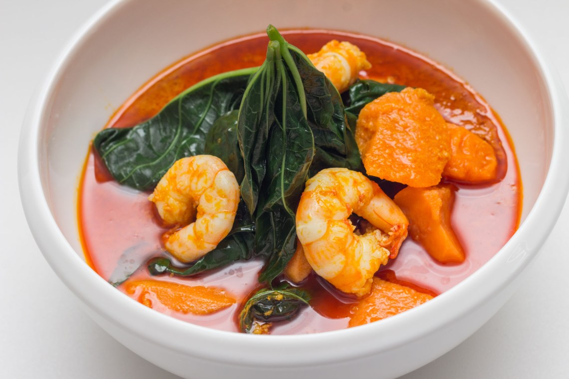 Photo shows a white bowl with three cooked prawns, sweet potato and sweet potato leaves in a reddish curry.