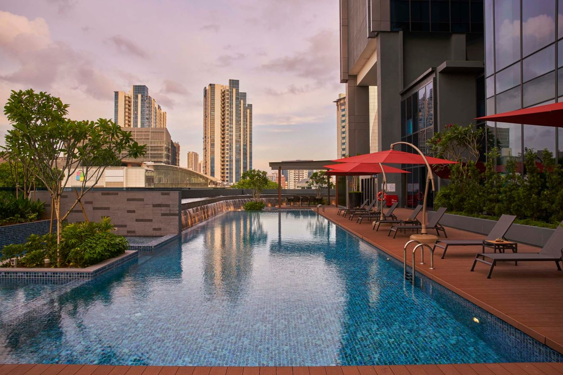 Photo shows a long lap pool on podium of Park Hotel Farrer Par, Singapore. In the background are two blocks of high rises with a dusky purplish sky.