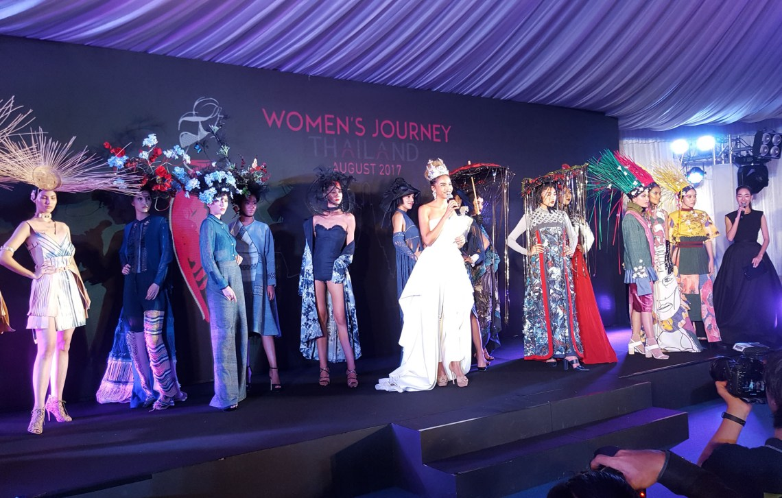 """Photos shows 12 women wearing designer wear on stage with woman in white gown identified as Winner of The FACE Thailand Season 3, Supermodel Natthaya """"Grace"""" Boonchompaisarn at the opening ceremony of the Women's Journey Thailand campaign 2017 on 1 August, 2017, at Nai Lert Park Heritage Home in Bangkok."""