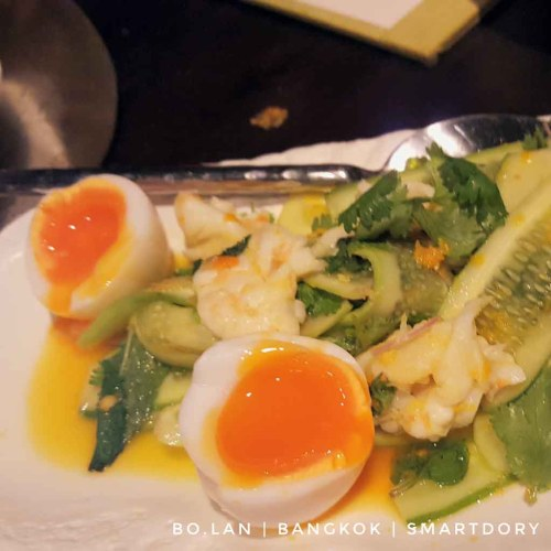 Soft boiled egg with runny yolk dressing for a cucumber, prawns and cilantro salad.