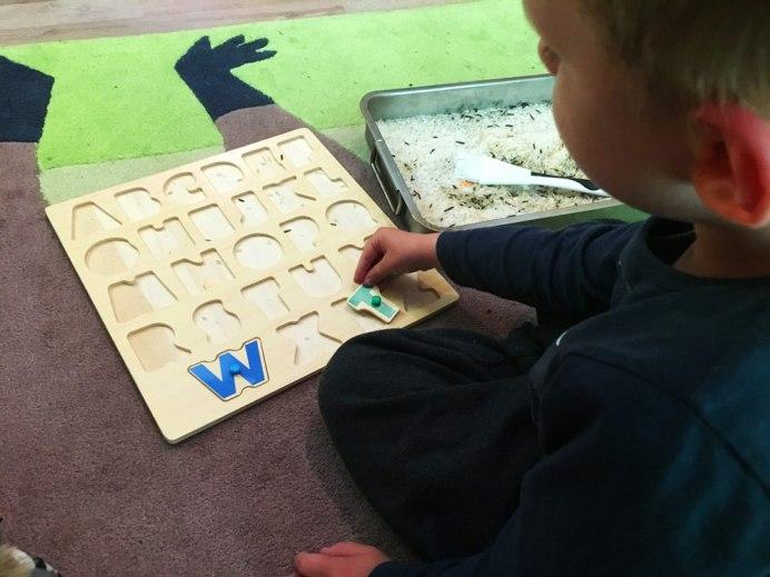 Wie Kinder lesen lernen : Kind spielt mit Buchstaben Puzzle. Die Buchstaben sind in einen flachen Gefäß unter Reis versteckt. Dieses Spiel ist einer der ersten Schritte zum Buchstaben und schließlich zum Lesen lernen.