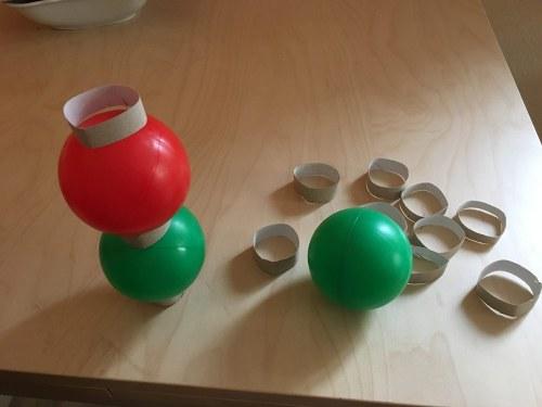 Ideen zur Beschäftigung für Kinder: Bällebadbälle werden mit Hilfe von zerschnitten Papprollenringen zu einen Turm gestapelt.