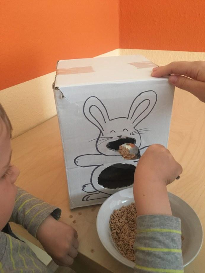 Gebasteltes Häschen wird von Kind mit Löffel mit trockenen Nudeln gefüttert
