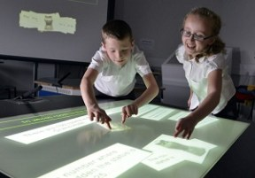 Dated: 22/11/12 Classroom of the Future... Researchers at Durham University who are designing and testing the 'classroom of the future' have found that multi-touch, multi-user desks can boost skills in mathematics. New results from a 3-year project working with over 400 pupils, mostly 8-10 year olds, show that collaborative learning increases both fluency and flexibility in maths. It also shows that using an interactive 'smart' desk can have benefits over doing mathematics on paper. The 'Star Trek classroom' could also help learning and teaching in other subjects. This picture shows Jamie Young (aged 8) and Jade Loveland (aged 8) from High Spen Primary School in Gateshead trying out the desks. #NorthNewsAndPictures/2daymedia