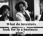 A black business woman shaking hands with caucusian investors look for in a business plan