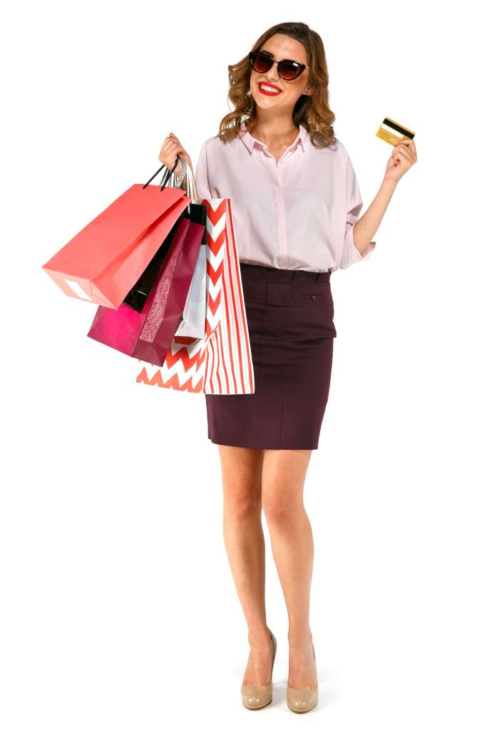 Black friday shopping by a causal smiling happy female wearing sunshads carrying shopping bags and holding credit card