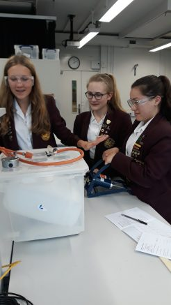 Grace Bartlett, Jess Ruddock and Kitty Underhill calculate the density of air.