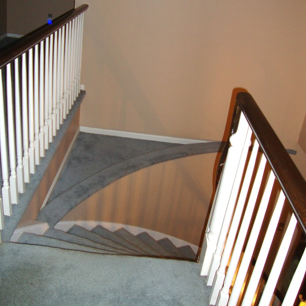 Curved staircase with triangle platform covered in carpet