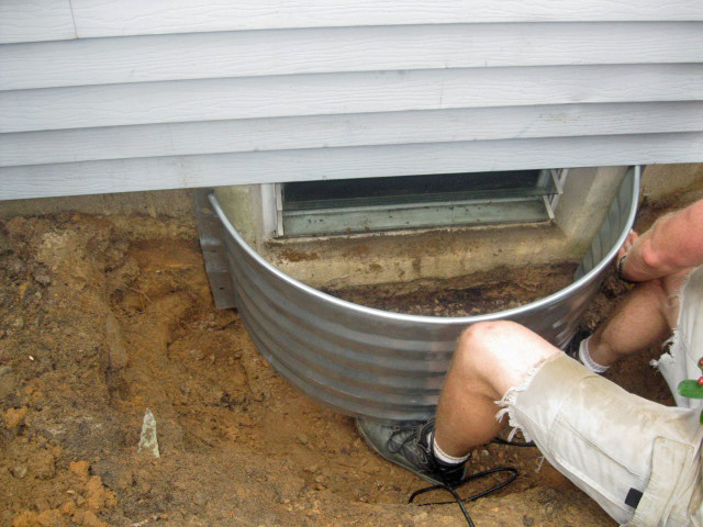 Attach prefabricated window well to foundation wall