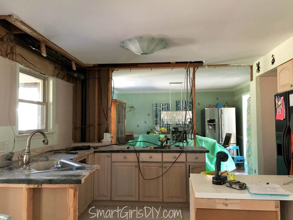 Kitchen demolition reveals pipes in wall between dining room and kitchen as well as in soffit