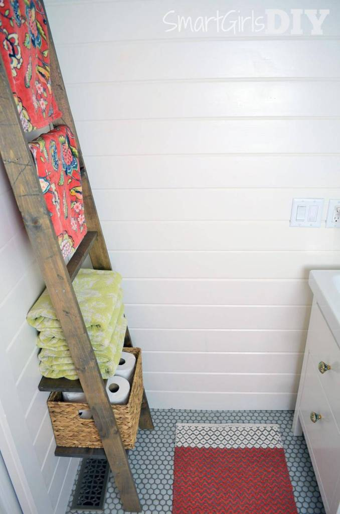 Extra shelf at bottom of DIY ladder to hold toilet paper basket