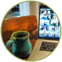 A laptop open to a Zoom meeting sitting on a table next to a teal coffee mug.