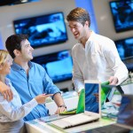 Young couple in consumer electronics store looking at latest lap