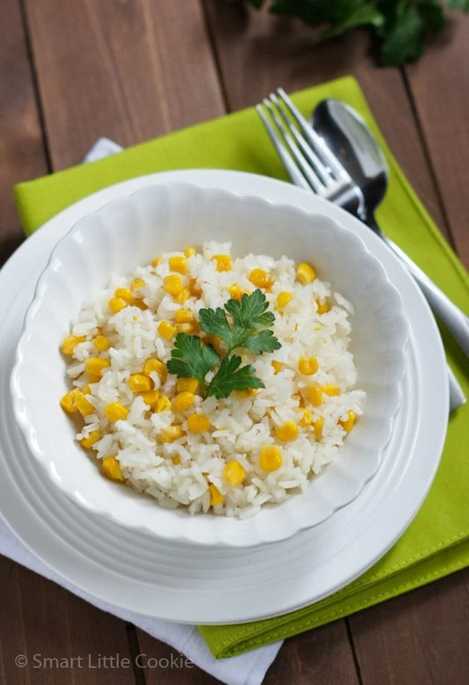 Rice served on a white bowl and topped with a parsley leave.