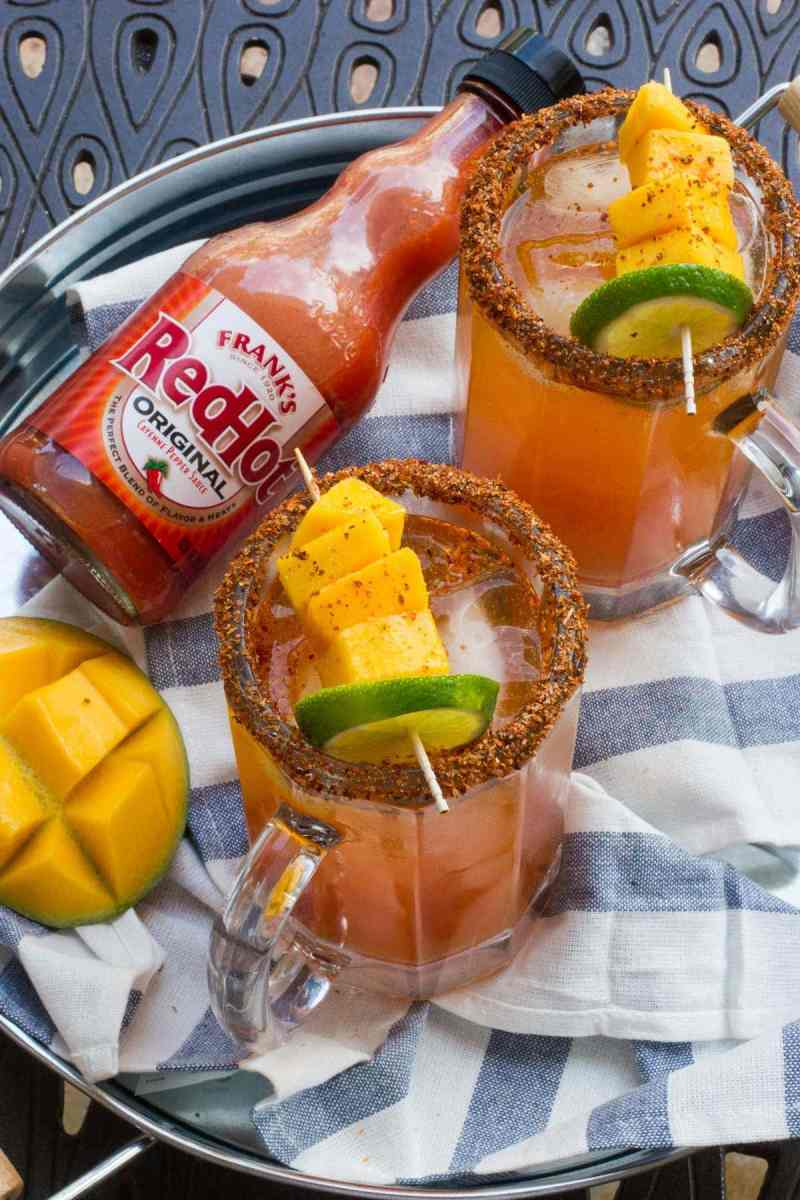 A sweet and spicy cocktail made with vegetable juice, mango tequila, Tajin, hot sauce and beer. This Spicy Mango Michelada is the perfect poolside drink this summer! #RedHotSummer #ad #IPSTOE