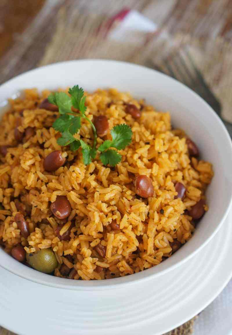 Rice with beans served on a white bowl and topped with cilantro leaves.