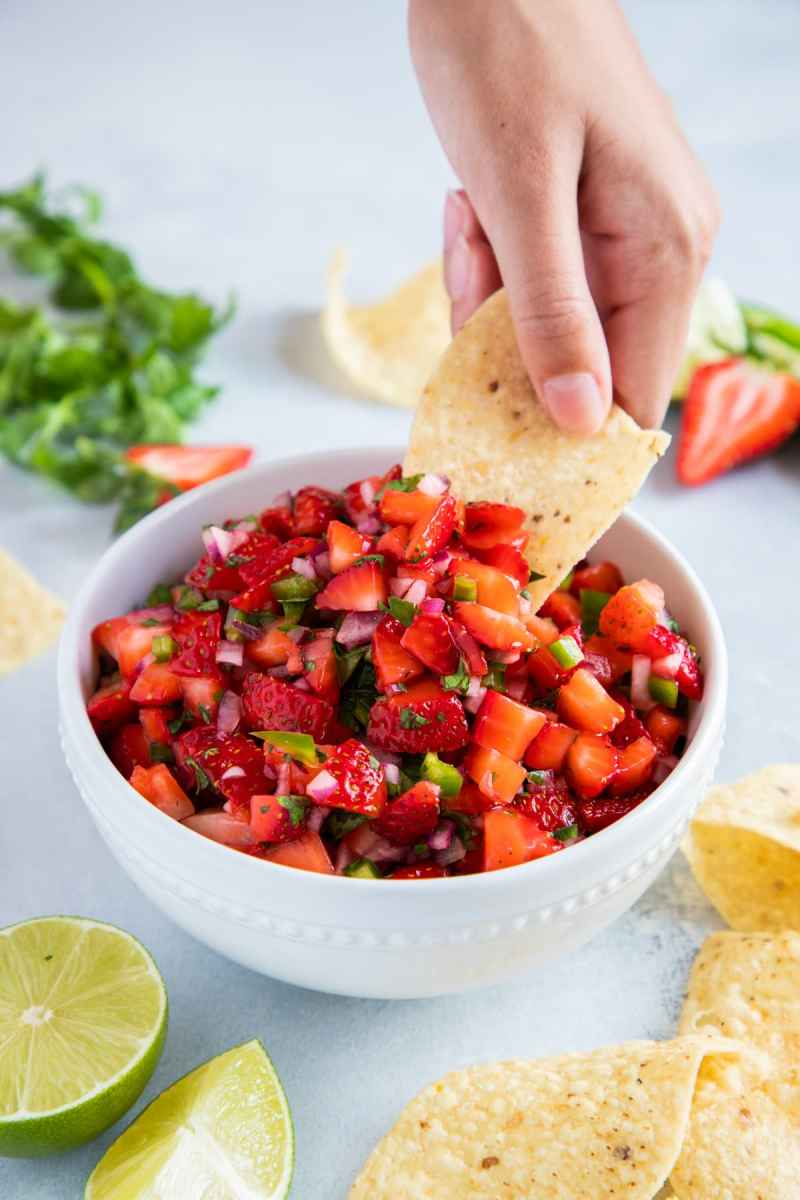 Hand dipping a corn chip into a bowl filled with Strawberry salsa.