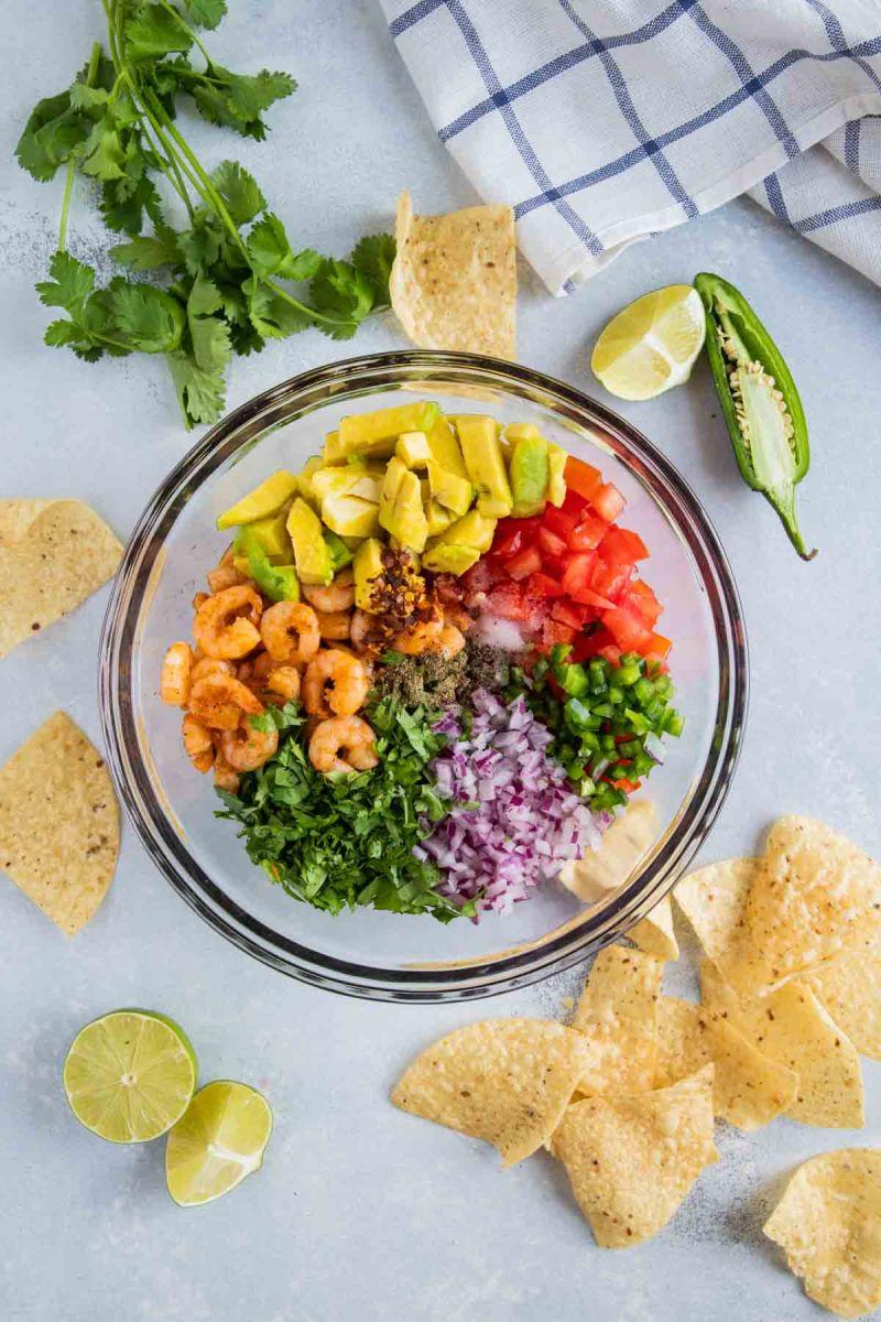 Ingredientes para prepara salsa de camarones con aguacate en un tazón de vidrio.