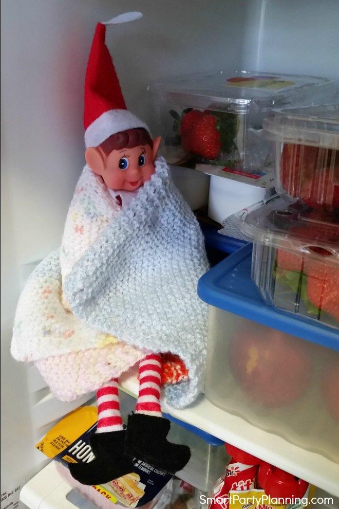 Elf on the shelf sits in the fridge
