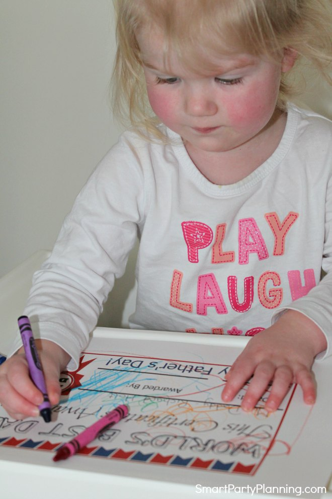Child completing a father's day certificate