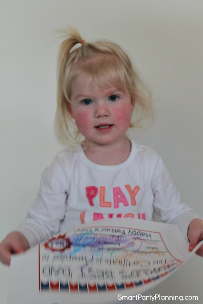 Child holding fathers day certificate
