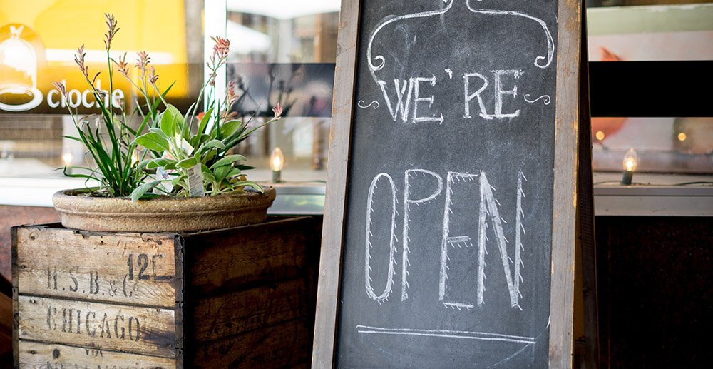 wooden we are open sign in front of small business customers attention