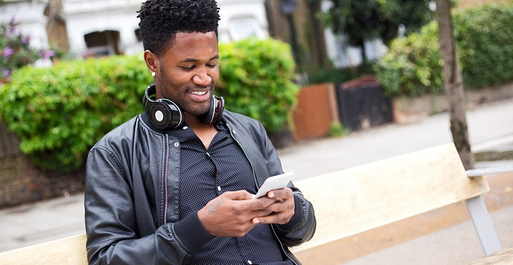 young man reading his text messages sat on a bench in the street touchpoint management