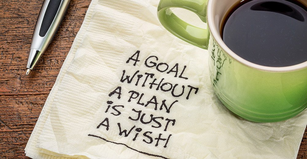 coffee cup on desk with napkin saying a goal without a plan is just a wish business objectives