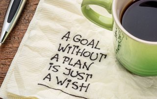 coffee cup on desk with napkin saying a goal without a plan is just a wish