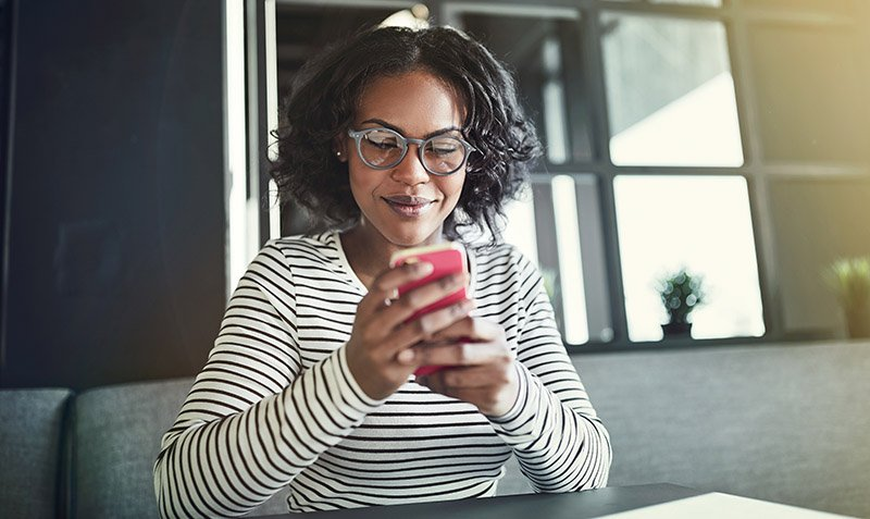 Young African woman wearing glasses smiling while sitting alone at a table reading a text message on her cellphone