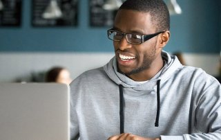 Smiling millennial african american casual man in glasses working with apps or communicating online on laptop sitting at cafe table, happy black businessman using public place wifi in coffee shop