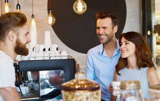 Couple at cafe talking barista, buying coffee