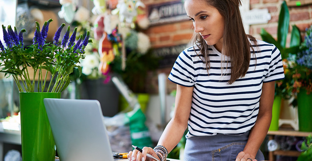 Portrait of young florist looking at client orders on laptop and notebook prevent stockouts