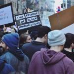 """Ανάμεσα σε άλλους διαδηλωτές κάποιος κρατάει ένα μαύρο χαρτόνι μα χαρτάκια που γράφουν τις λέξεις: """"This episode of black mirror sucks"""""""