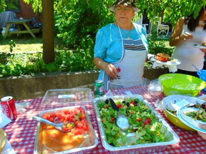 Maria helps serve salads to tenants