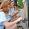 Senior Elizabeth Birkenmeier and Junior Halle Connelly paint the space around the wheels on the float. Photo by Abby Hans