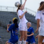 Junior Lilly Flint jumps up for a header to keep the ball from Olathe-South. Photo by Kaitlyn Stratman