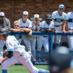 Teammates watch from the dugout as junior Luke Anderson gets thrownout at home plate. Photo by Spencer Carey
