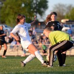 Freshman Caroline Chisholm attempts to kick the ball as the opposing goalie picks it up. Photo by Katherine Odell