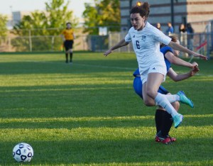 Sophomore Izzy Rapp trips over her opponent while running for the ball. Photo by Ellen Swanon