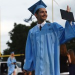 Senior Diego Galicia smiles and waves after accepting his diploma. Photo by Drake Woods