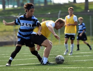 Senior Cooper McCullough is blocked by an alumni soccer player as he looses possession of the soccer ball. Photo by Katherine Odell