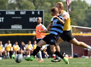 Beating his defender to the goal, junior Cooper Holmes positions his body towards the goal to get a shot off. Photo by Lucy Morantz